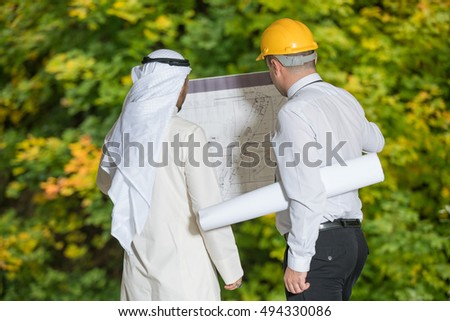 Professional engineer in a hardhat going through the building plan with his business client