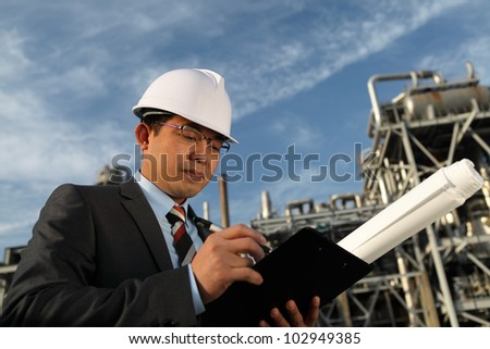 Professional engineer oil gas industry write on note board with large oil industry in the background and blue sky