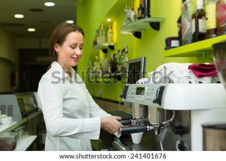 Professional female barista smiling near coffee machine
