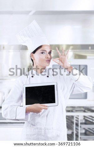 Professional female chef showing deliciousness gesture while holding a digital tablet in the kitchen - stock photo