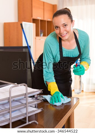Professional female cleaner cleaning at office with sprayer