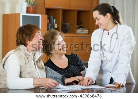 Professional female doctor consulting mature women in clinic interior