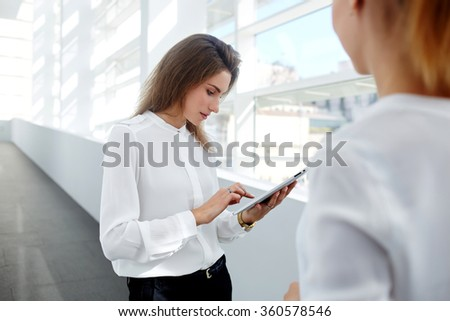 Professional female employee working on digital tablet while her partner standing near in modern office interior, elegant businesswoman use touch pad for search information in Internet for colleague - stock photo