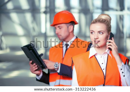 Professional female engineer is talking on the phone and discussing building with the customer. The woman is smiling. The builder is standing behind her and using a tablet with concentration - stock photo