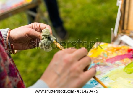 Professional female painter  working on a canvas outdoors cleaning off her paintbrush with a rag