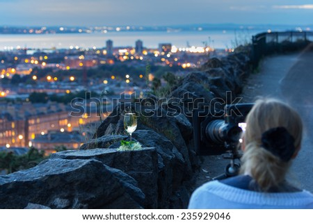 Professional female photographer with digital SLR during photography workshop. Image with focus on wine glass - stock photo