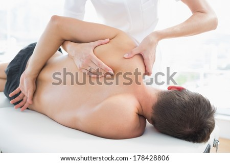Professional female physiotherapist giving shoulder massage to man in hospital - stock photo
