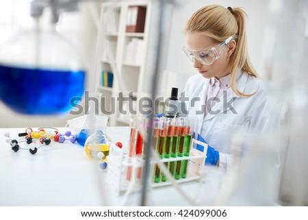 Professional female scientist is examining medical sample - stock photo