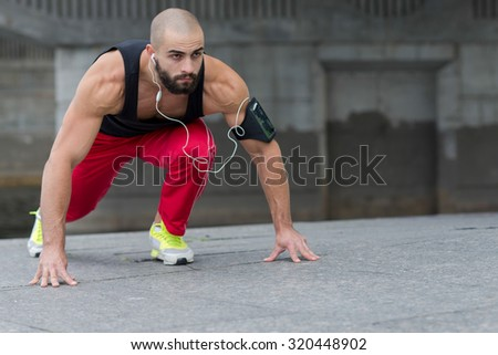 Professional fitness athlete trainer. Muscular male sportsman is training himself. Man is running. Outdoors fitness sport concept. Street workout in headphones - stock photo