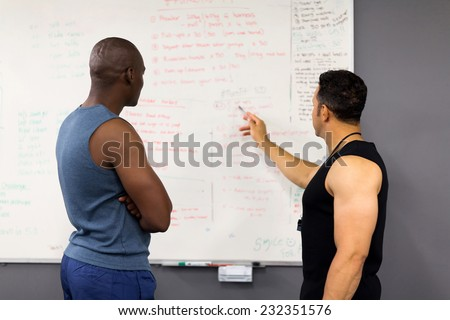 professional fitness coach planning gym session with client - stock photo