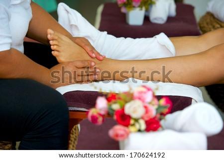 professional foot massage in Thai massage salon - stock photo