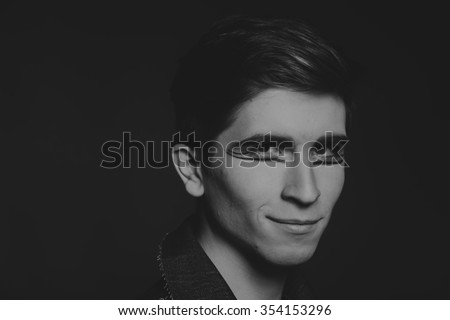 Professional game young actor. Black and white photo on a dark background. Professional makeup and theatrical image. Photo for cultural and fashion magazines and websites.