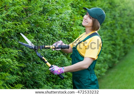 professional gardener at work. smiling young woman gardener working with hedge shear in the yard. garden worker trimming plants. topiary art. gardening service and business concept