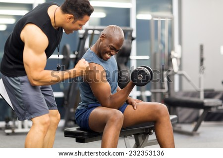 professional gym trainer motivating client to lift dumbbell