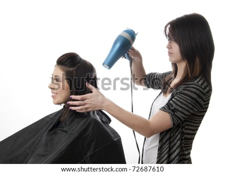 Professional hair stylist blowing out client's hair - stock photo
