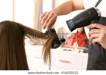 Professional hairdresser drying hair - stock photo