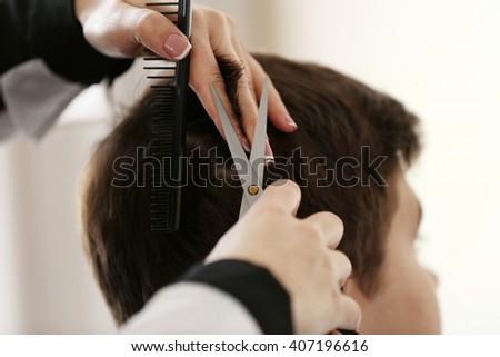 Professional hairdresser making stylish haircut, closeup - stock photo