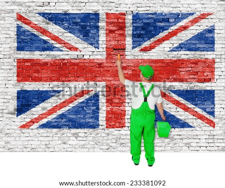 Professional house painter covers brick wall with british flag  - stock photo