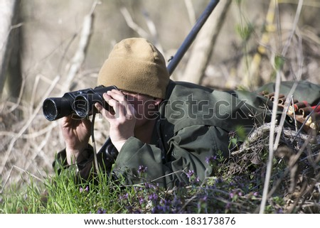 Professional hunter looking through binoculars  - stock photo