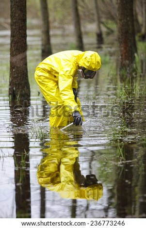 professional in protective coveralls taking sample of water to container in floods contaminated area - stock photo