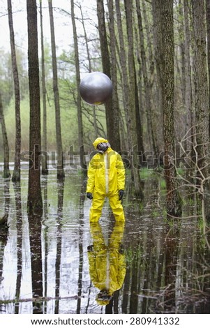 professional in protective uniform, mask, gloves with silver sphere drone above his head   in contaminated  floods area - stock photo