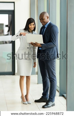 professional indian businesswoman with african businessman using laptop in modern office - stock photo