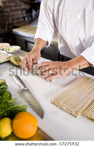 Professional Japanese chef in restaurant making sushi rolls - stock photo