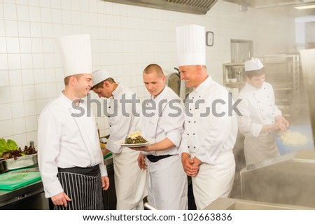 Professional kitchen busy team cooks and chef prepare meal - stock photo