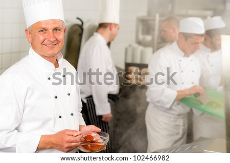 Professional kitchen smiling chef cook add spice paprika prepare food meals - stock photo