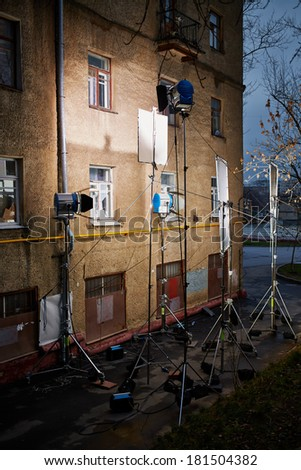 Professional lighting equipment - floodlights, reflecting screens - mounted near old house wall - stock photo
