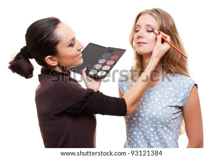 professional make-up artist applying eye shadow. isolated on white background - stock photo