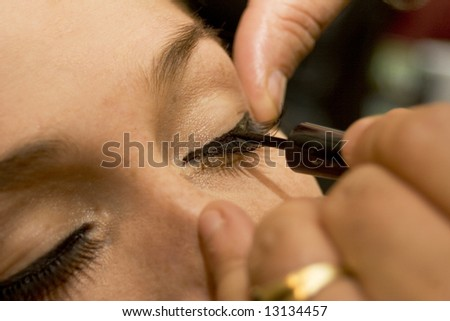 Professional make-up artist applying liner to eyes