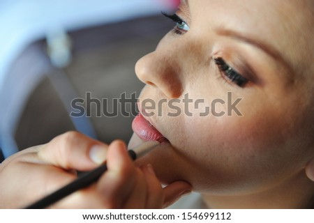 Professional make up artist applying make up to a fashion model / bride.  - stock photo