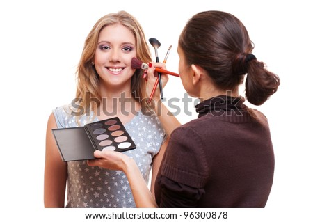 professional make-up artist working with model. studio picture over white - stock photo