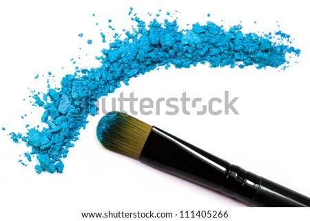 Professional make-up brush on blue crushed eyeshadow - stock photo