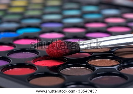 Professional make-up brush on color shadows in red texture
