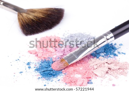 Professional make up brushes on colour eyeshadows, closed-up on white