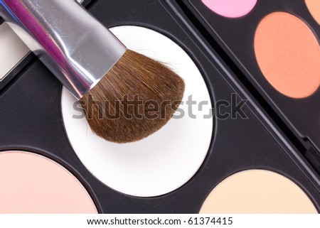 Professional make-up brushes on eyeshadows palettes, closed-up