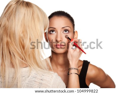 Professional makeup artist applying makeup to model's face - isolated on white - stock photo