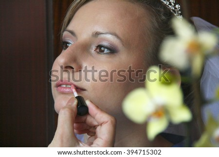 Professional makeup artist applying red lipstick on a fashion model lips
