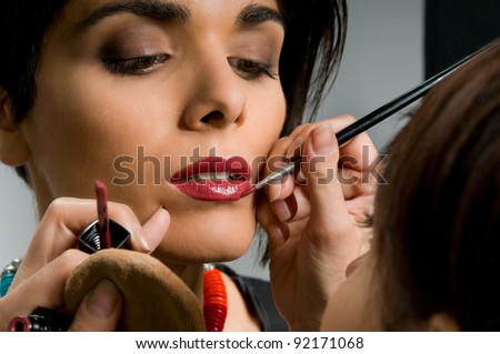 Professional makeup artist applying red lipstick on a fashion model lips before the stage - stock photo