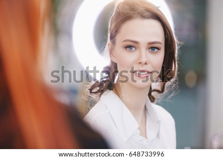Professional makeup artist working with beautiful young woman and doing make-up