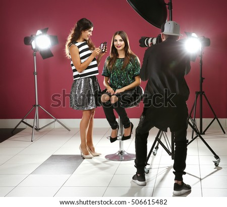 Professional makeup artist working with young beautiful woman at photo shooting