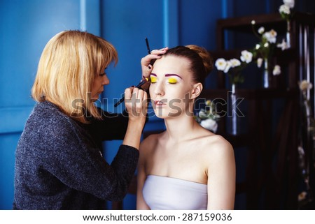 Professional makeup process. Artist is making face style of a young beautiful model at  blue studio background. - stock photo