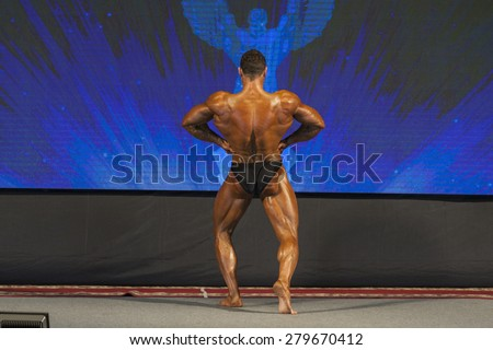 Professional Male Caucasian Bodybuilder Performing on Stage. Back View. Horizontal Image Composition - stock photo