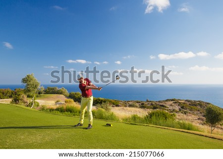 Professional male golf player hitting by driver from tee