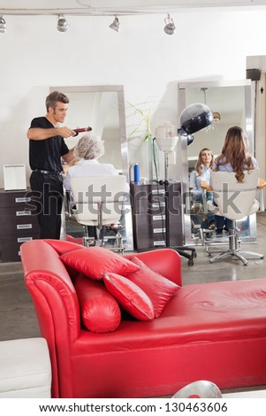 Professional male hairdresser styling customer's hair with female client waiting at parlor - stock photo