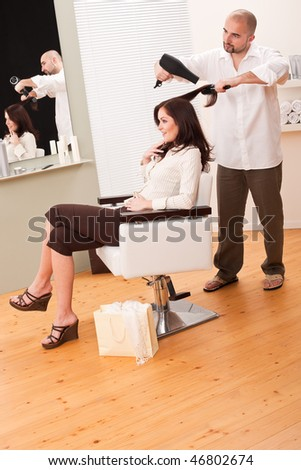 Professional male hairdresser with hair dryer and hair brush at salon with female customer, shopping bag on floor