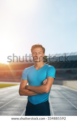 Professional male track athlete standing with his arms crossed looking at camera. Runner standing in lane at the athletics track in a outdoor athletics stadium with sun flare. - stock photo