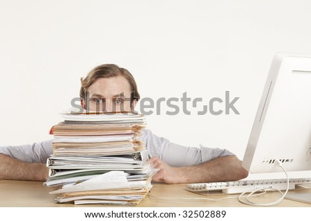 professional man sitting at desk behind stack of paperwork - stock photo
